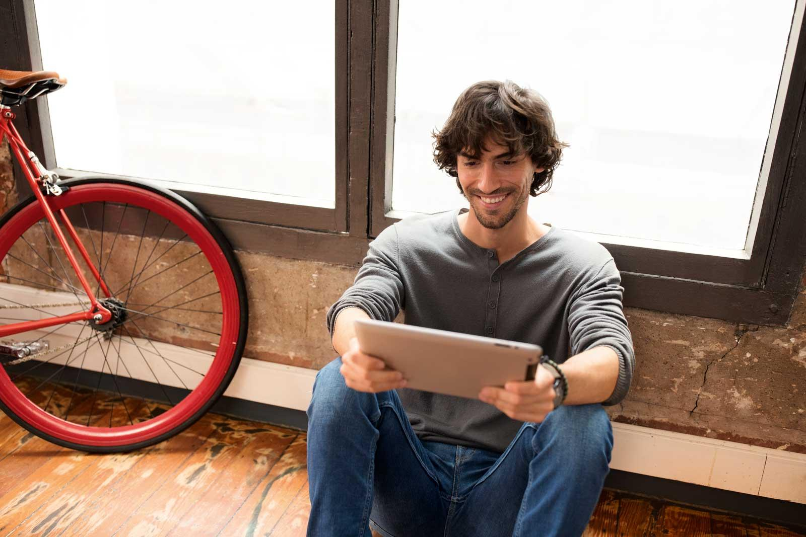 young-man-sitting-on-floor-bike