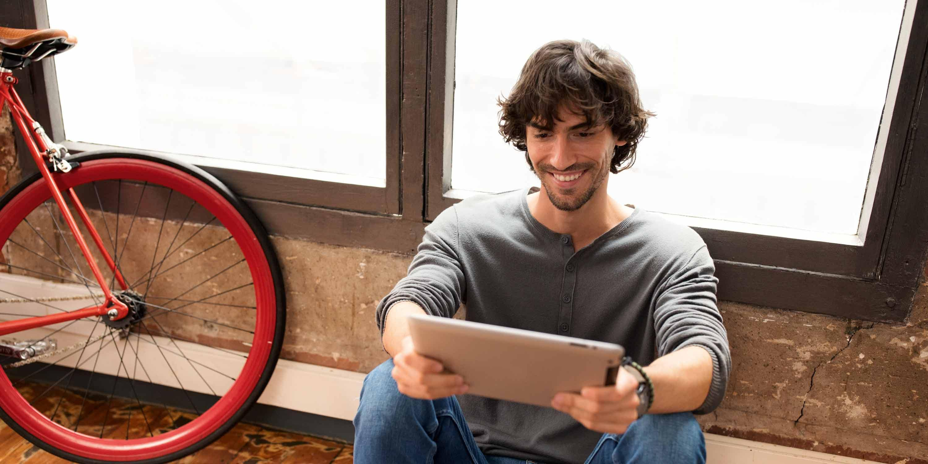 man-sitting-in-front-of-window-with-tablet-stage.jpg